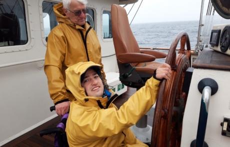 Brian Murphy at the wheel of the tall ship Tenacious